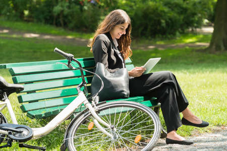 Smiling Young Businesswoman Sitting On Bench Using Digital Tablet At Park