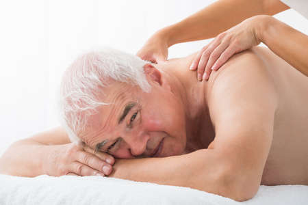 old man on a physical pressure: Close-up Of A Senior Man Receiving Back Massage In Spa Stock Photo