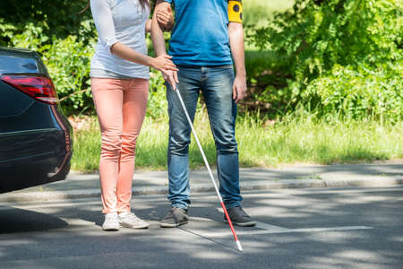 blind man: Woman Assisting Blind Man With White Stick On Street Stock Photo