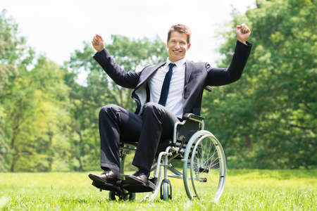 wheelchair access: Happy Young Disabled Man On Wheelchair With Raised Arms In Park