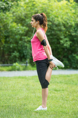 Young Woman Stretching Her Legs While Exercising In Park