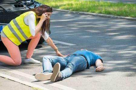 Femme appelant à l'aide d'urgence Regardant Blessé Man Après Accident