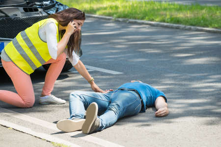 Woman Calling For Emergency Help Looking At Injured Man After Accident Stock Photo