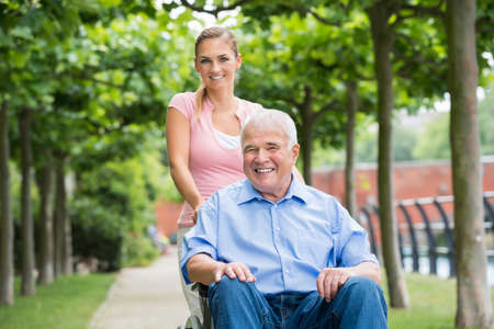 Gelukkige jonge vrouw met haar oude Senior Vader op rolstoel in Park Stockfoto