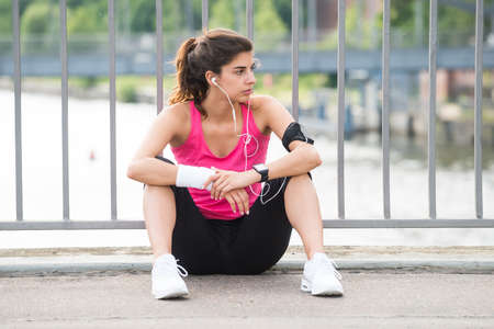 Young Contemplated Fitness Woman Listening To Music On Headphone