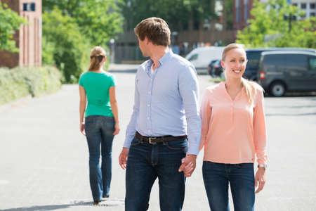 Junger Mann mit seiner Freundin auf der Walking Street an einer anderen Frau Auf der Suche