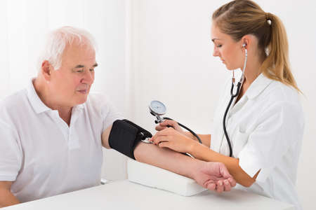 Young Female Doctor Checking Blood Pressure Of Senior Male Patient In Clinic Stock Photo