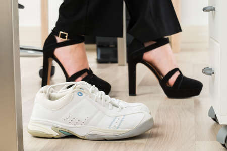 sport shoe: Pair Of A White Sport Shoes Besides Businesswomans Foot Wearing High Heels