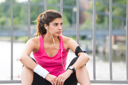 contemplated: Young Contemplated Fitness Woman Listening To Music On Headphone