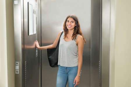 Smiling Young Woman Standing In Elevator And Pressing Button Stock Photo - 61867621
