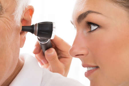 otoscope: Close-up Of Female Doctor Examining Patients Ear With Otoscope