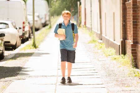 school teens: Portrait Of Happy Schoolboy With Books On Sidewalk Stock Photo