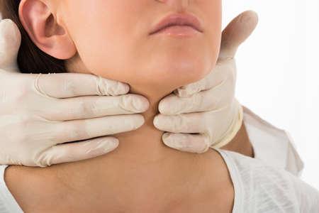 Un medico esegue esame palpazione fisica della tiroide Archivio Fotografico