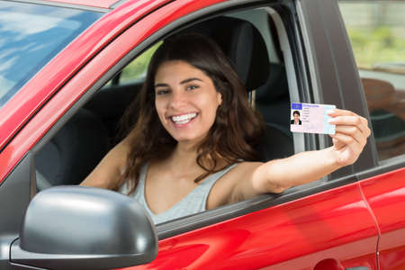 Smiling Young Woman Showing Her Driving License From Open Car Window Stock Photo