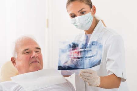 persona de la tercera edad: Jóvenes mujeres médico Mostrando Dental X-ray a paciente de sexo masculino mayor en la Clínica Foto de archivo