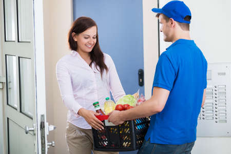 Smiling Young Woman Receiving Groceries From Delivery Man At Home