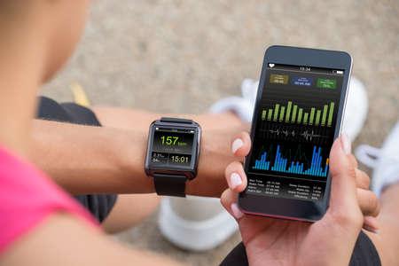 Corredor femenino que mira a su móvil y elegante reloj monitor de ritmo cardíaco