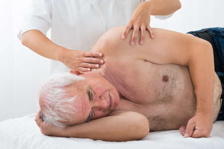 Close-up Of Therapist Giving Massage To Senior Man In Spa