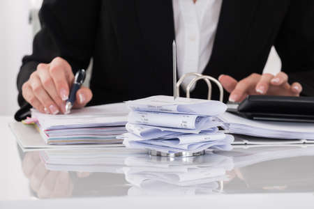 stack of paper: Close-up Of Female Accountant Calculating Tax At Desk