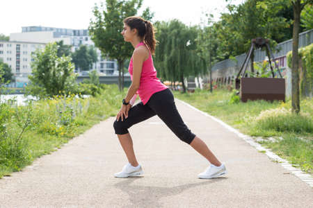 Photo Of Young Fitness Woman Stretching In Park