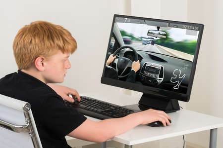 kids playing video games: Boy Sitting On Chair Playing Car Game On Computer At Home