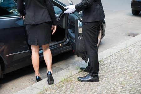 abertura: Chofer Hombre de abrir la puerta del coche para La Empresaria En la calle Foto de archivo