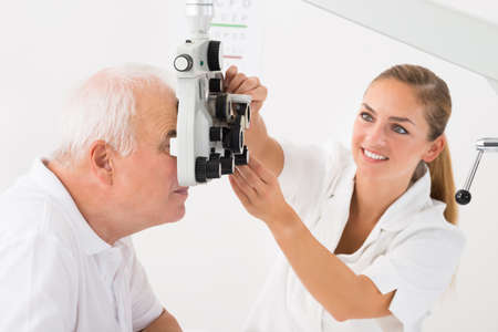 medical man: Happy Female Optometrist Doing Sight Testing For Patient In Clinic