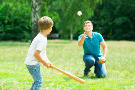 Little Boy Playing Baseball With His Father In Park Foto de archivo