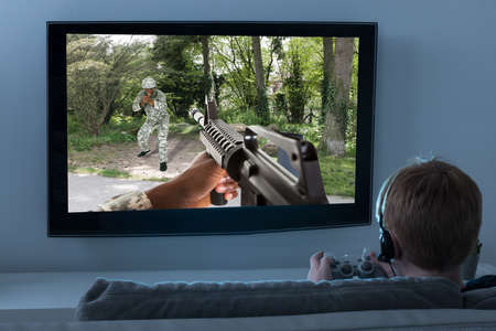 Menino senta-se no sofá que joga Action Game On Television
