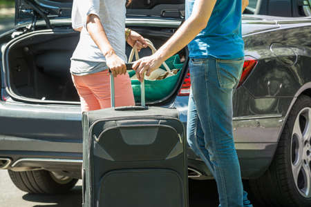 Close-up Of Couple Putting Luggage In A Car Trunk Imagens