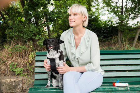 retractable: Young Happy Woman Sitting With Her Dog On The Bench