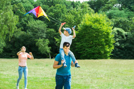 family in park: Family Enjoying In The Park While Flying The Colorful Kite Stock Photo