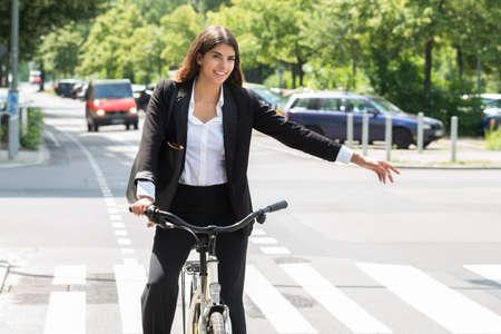 Sonriente joven empresaria gire en bicicleta en la calle