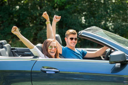 cabrio: Happy Couple Sitting In A Car Wearing Sunglasses Raising Their Arms