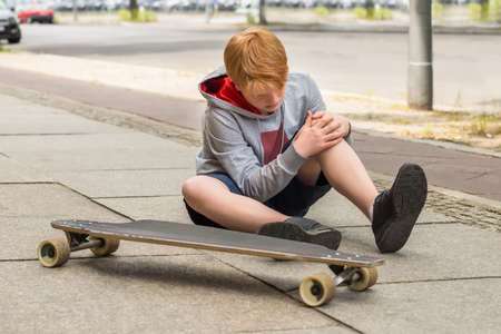 Jongen Bij Zijn geblesseerde been zitten in de buurt Skateboard zoek