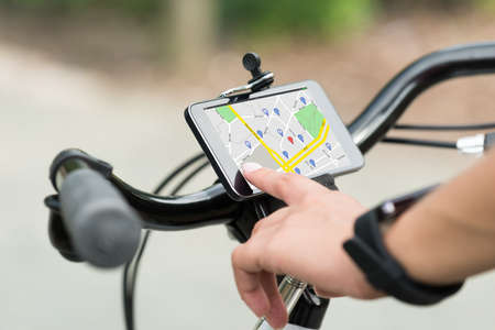 portables: Close-up Of Human Hand Pointing At Smart Phone Showing GPS Navigation On Bicycle Stock Photo