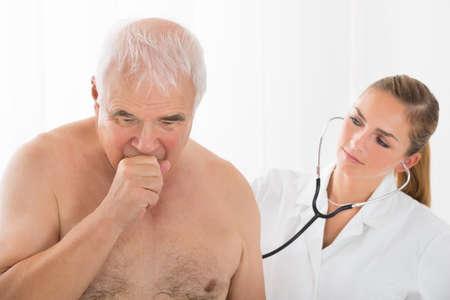 tosiendo: Jóvenes mujeres médico usa el estetoscopio en Volver Senior paciente masculino