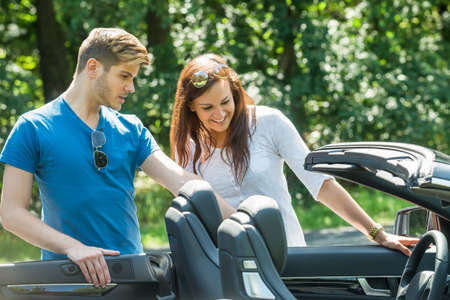 purchased: Smiling Young Couple Looking At Their Newly Purchased Car