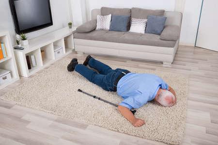 Inconscient homme senior Disabled Allongé sur le tapis à la maison