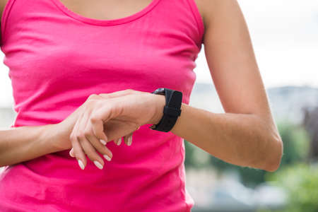 Close-up Of Sporty Young Woman Touching At Her Smart Watch