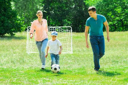 pelota de futbol: Familia feliz que juega con el balón de fútbol en el parque