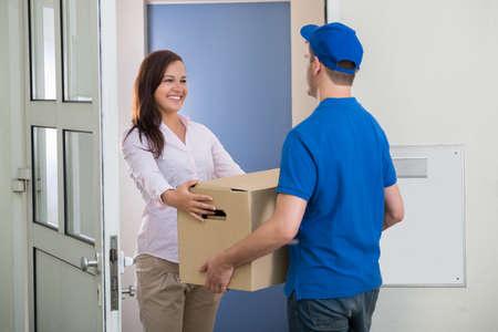 Mujer feliz que recibe un paquete desde la entrega uno a la puerta Foto de archivo