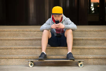 teenage problems: Boy Wearing Cap Sitting On Staircase Looking At Cellphone