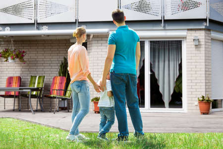 outside house: Rear View Of A Family Standing In Front Of Their New House Stock Photo