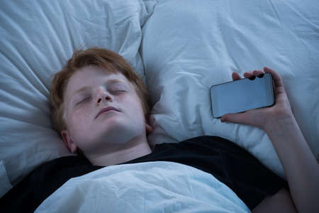 portables: Boy Sleeping On Bed With His Mobile Phone Stock Photo