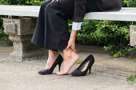 Close-up Of Businesswomans Hand Sitting On Bench Removing High Heels Stock Photo