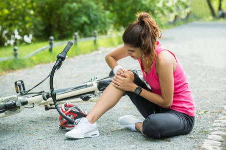 Mujer joven con dolor en la rodilla Cuando caído De bicicletas