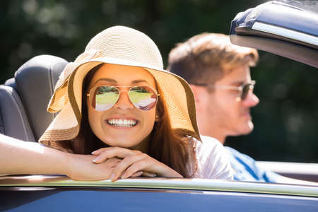 cabrio: Smiling Woman Wearing Sunglasses Enjoying Ride In A Car Stock Photo