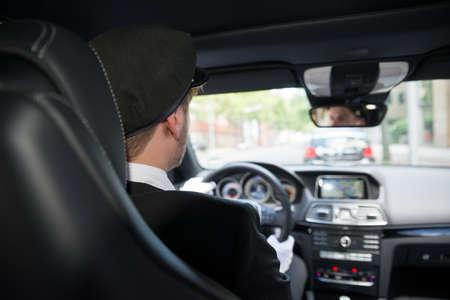 chauffeur: Rear View Of A Male Chauffeur Driving A Car