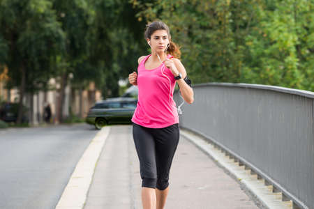 Sporty Young Woman Running On Sidewalk In Morning